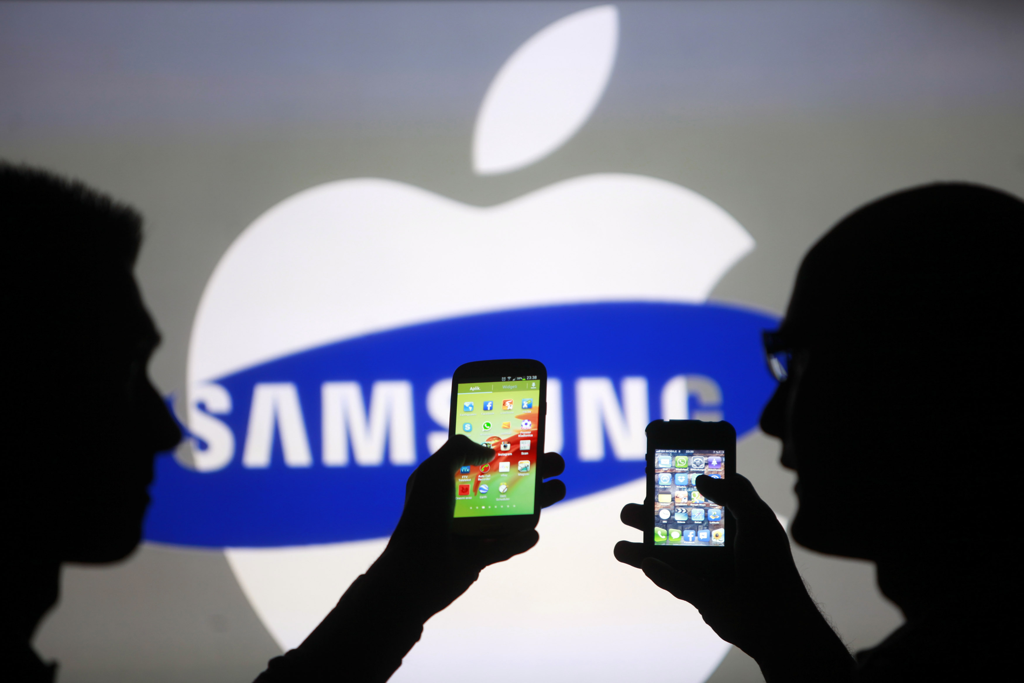 Men are silhouetted against a video screen as they pose with Samsung Galaxy S3 and iPhone 4 smartphones in this photo illustration taken in the central Bosnian town of Zenica, May 17, 2013. REUTERS/Dado Ruvic (BOSNIA AND HERZEGOVINA - Tags: BUSINESS TELECOMS) - RTXZQ3W