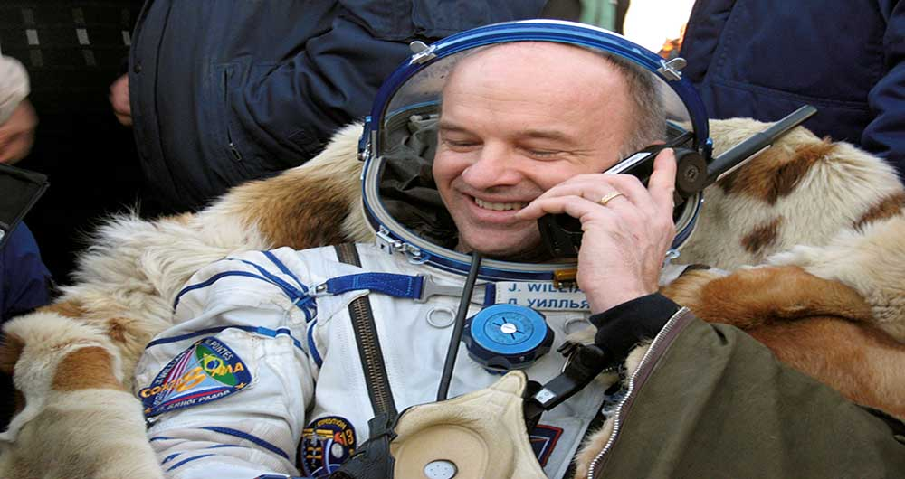 While talking on a telephone, Army Astronaut Col. Jeffrey N. Williams, Expedition 13 flight engineer and NASA ISS science officer, is surrounded by Russian and American search and recovery teams on the steppe of central Kazakhstan Sept. 29. This came a short while after the landing in the Soyuz TMA-8 spacecraft following undocking earlier in the day from the International Space Station.  Williams and Cosmonaut Pavel V. Vinogradov, Expedition 13 commander, spent 183 days in space.