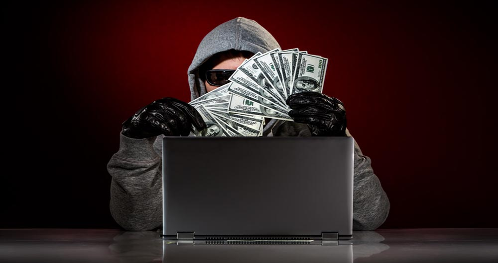 Young hacker in a sunglasses with laptop and money in hand