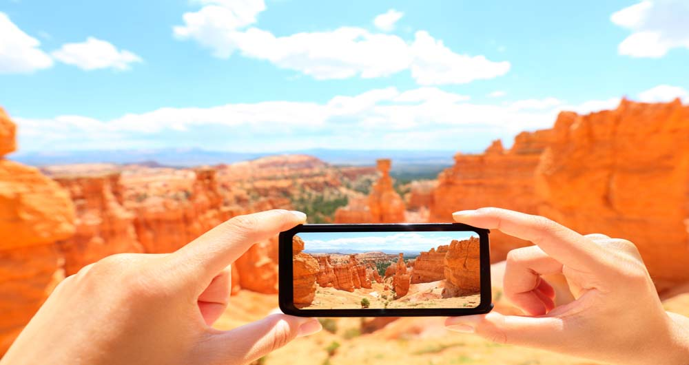 Smartphone taking photo of Bryce Canyon nature. Close up of mobile phone camera screen photographing beautiful american landscape Bryce Canyon, Utah, USA.