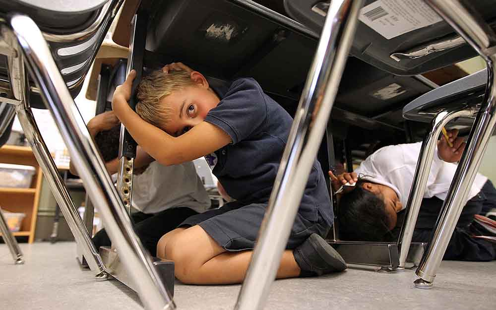 Third grade students at William L. Cobb Elementary School take cover under desks as they participate in the Great California ShakeOut earthquake drill on Oct. 20, 2011.