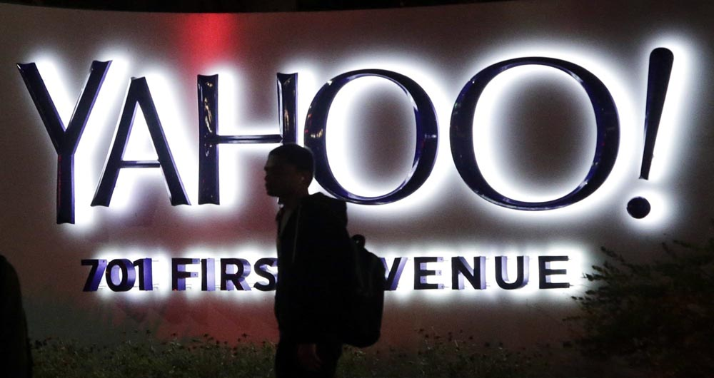 FILE - In this Nov. 5, 2014, file photo, a person walks in front of a Yahoo sign at the company's headquarters in Sunnyvale, Calif. Verizon has agreed to buy online portal Yahoo Inc. for roughly $5 billion, according to multiple media reports sourcing unnamed sources. The deal is expected to be announced formally on Monday, July 25, 2016, before markets open. (AP Photo/Marcio Jose Sanchez, File)