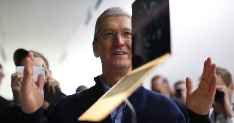 san-francisco-ca-march-9-apple-ceo-tim-cook-stands-in-front-of-an-macbook-on-display-after-an-ap