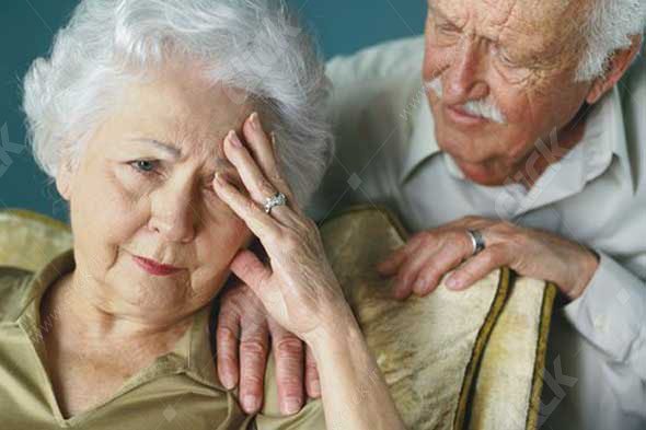 close-up of an elderly man consoling his wife